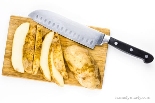 Cut up russet potatoes on a cutting board with a knife.