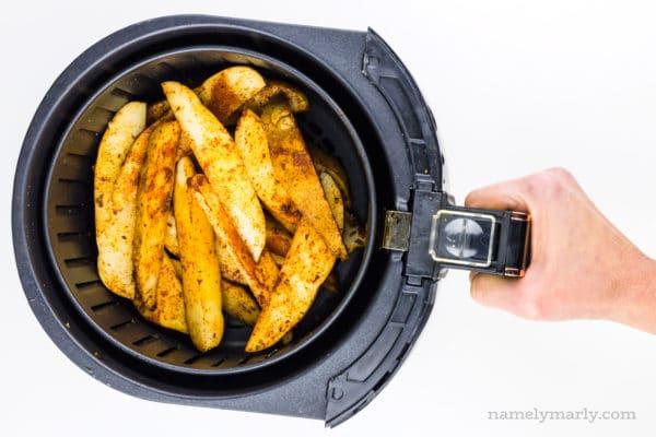 Season potato wedges are in an air fryer basket.