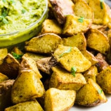 Air fryer potatoes sit next to a bowl of green sauce for dipping.