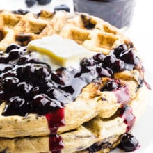 A stack of blueberry waffles has vegan butter on top and some blueberry sauce. There are fresh blueberries and a bowl of more blueberry sauce behind it.