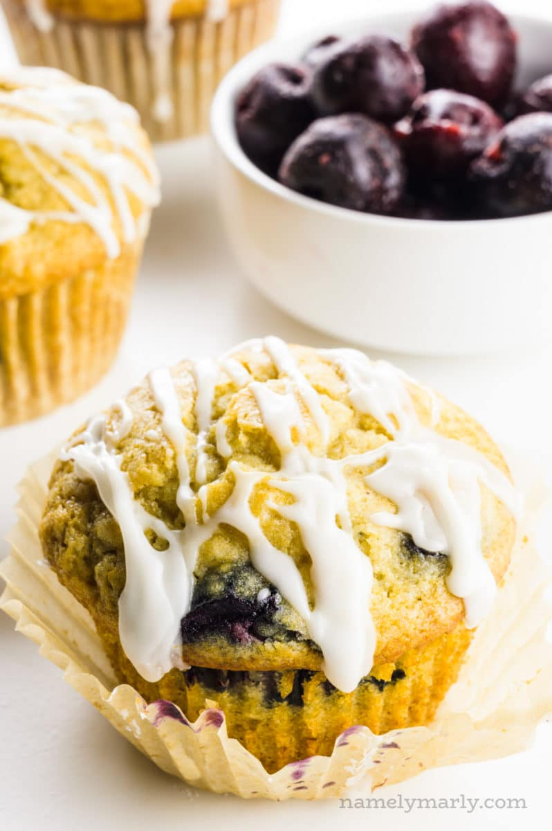 A muffin has lots of frosting drizzled on top with more muffins behind it and a bowl of frozen cherries.