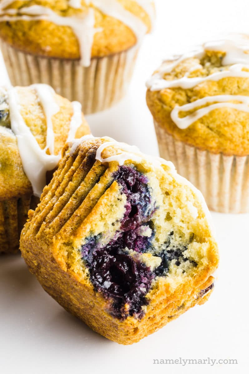 A cherry muffin with a bite taken out of it sits in front of other muffins.