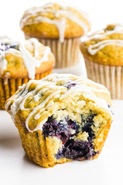 A cherry muffin with a bite taken out of it sits in front of three other muffins.
