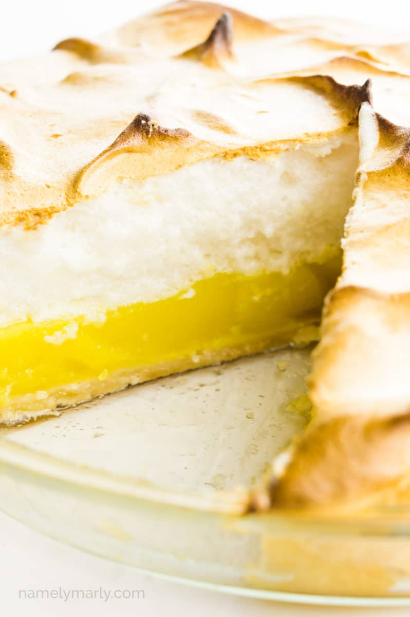 A lemon meringue pie has a slice cut out, showcasing layers of lemon curd and meringue on top.