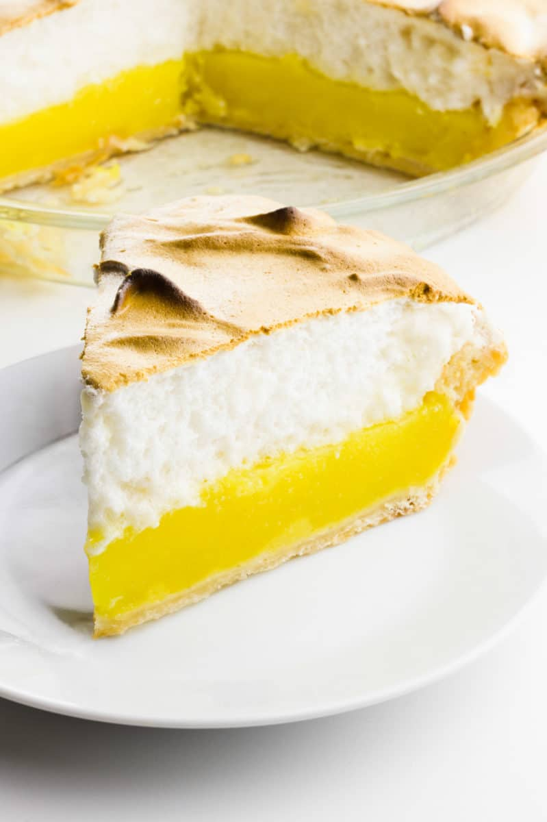 A slice of lemon meringue pie on a plate sits in front of the rest of the pie.