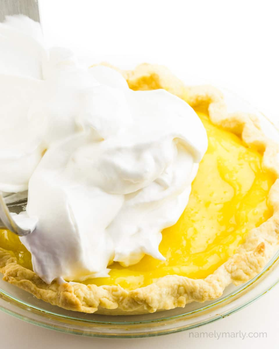 A bowl is pouring meringue over the top of a lemon pie.