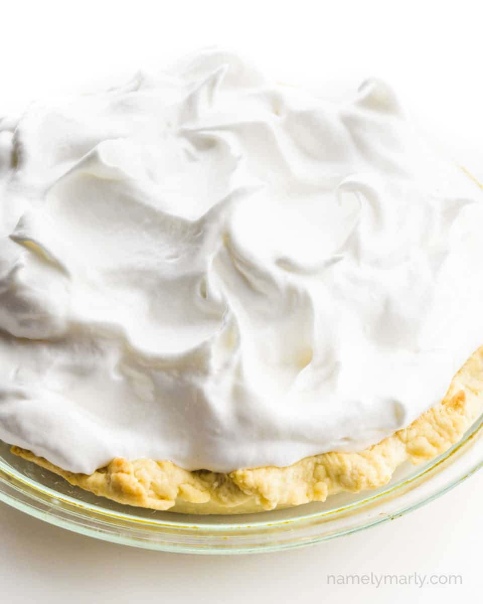 A lemon pie is topped with unbaked meringue.