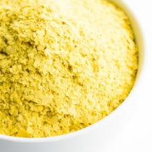 A bowl is full of yellow nutritional yeast flakes.