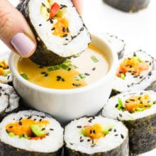 A hand holds vegan sushi, dipping it in a bowl with sauce. There's more sushi rolls around the bowl.