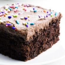 A slice of chocolate wacky cake has frosting and sprinkles on top.