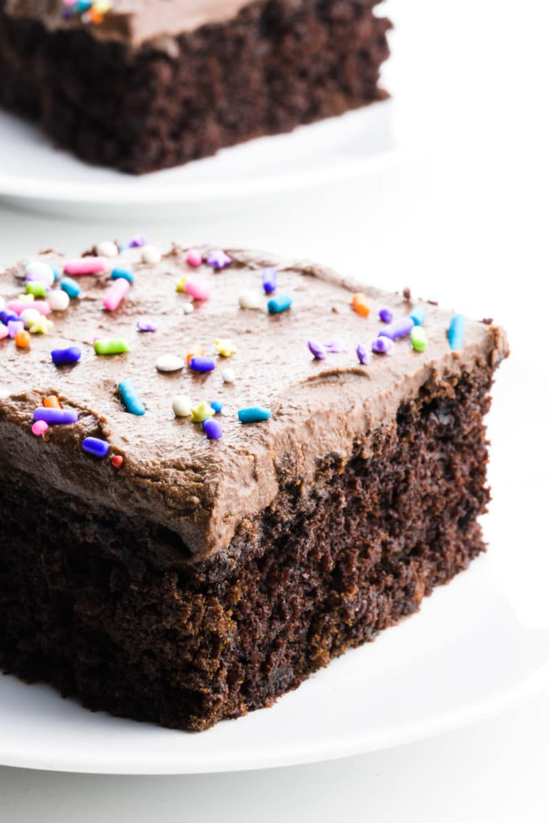 A slice of chocolate cake has frosting and sprinkles on top. Another slice sits behind it.