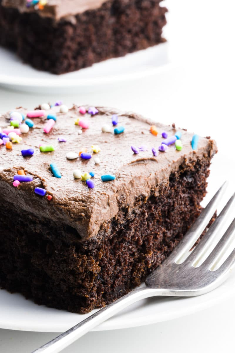 A fork sits beside a slice of wacky cake with chocolate frosting and sprinkles. Another slice of cake sits on a plate behind it.