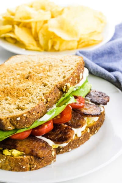 A sandwich has layers of ingredients, including tempeh bacon, tomatoes, lettuce and mayo. There's a plate of potato chips next to a blue kitchen towel in the background.