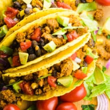 Three tacos are next to each other with ingredients all around, like cherry tomatoes, greens, and more.