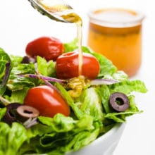 A spoon pours dressing over a salad. A jar with more dressing sits behind it.