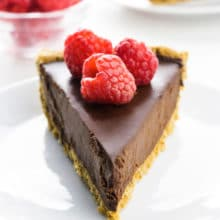 A slice of chocolate pie on a plate has a bowl of raspberries and another slice of pie behind it.