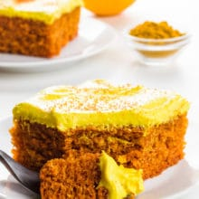 A slice of turmeric cake sits on a plate with a bite sitting on a fork. An orange and a small bowl of turmeric is behind it.