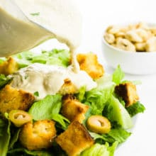 A serving dish full of vegan caesar dressing is being poured over a salad. There's a bowl of cashews in the background.