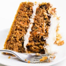 A slice of carrot cake sits on its side on a plate with a fork in front of it.
