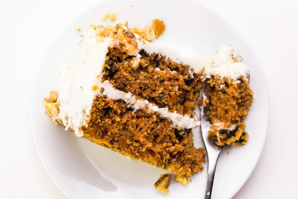 Looking down on a plate with a slice of carrot cake on it. A fork has cut into the cake and is sitting at the front of the plate.