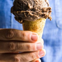 A hand holds a cone full of a large scoop of vegan chocolate ice cream. The person holding it has on a blue top.