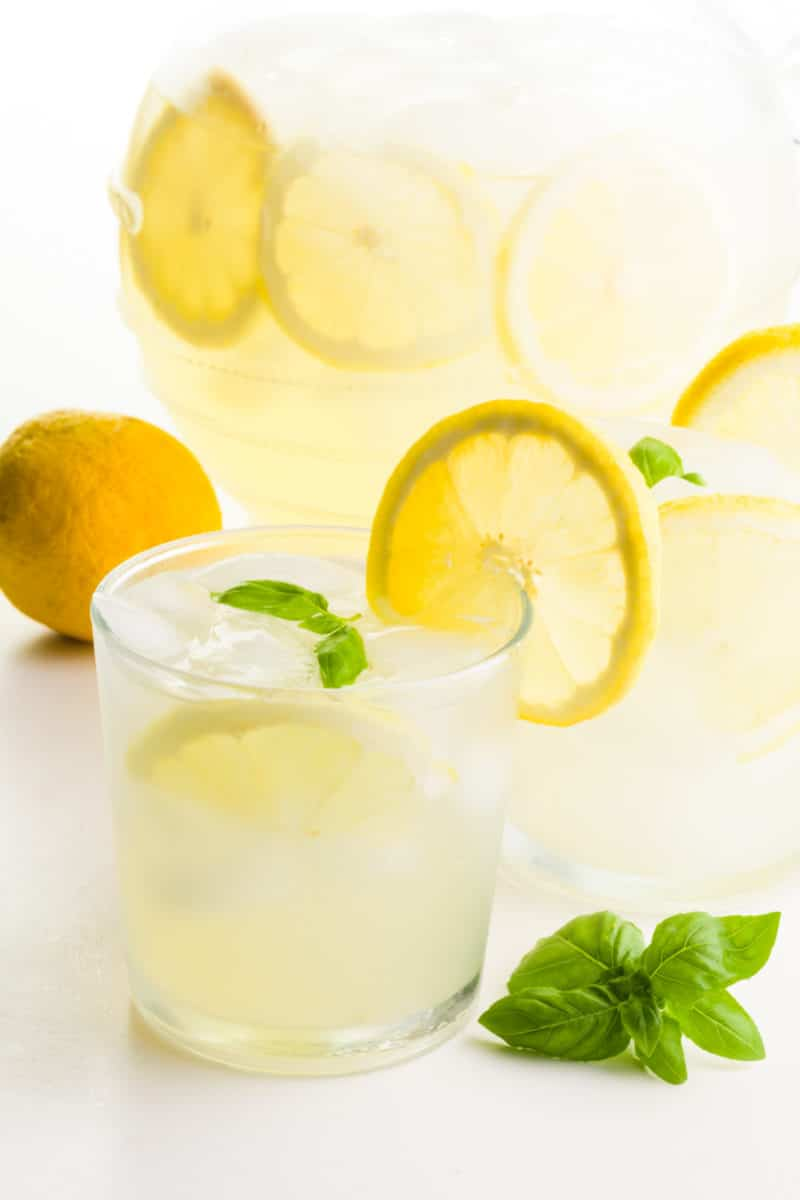Two glasses of lemonade have fresh lemon slices on the glasses. There's a lemon behind it, and basil sprigs in front of it. There's a pitcher of more of the beverage behind it.