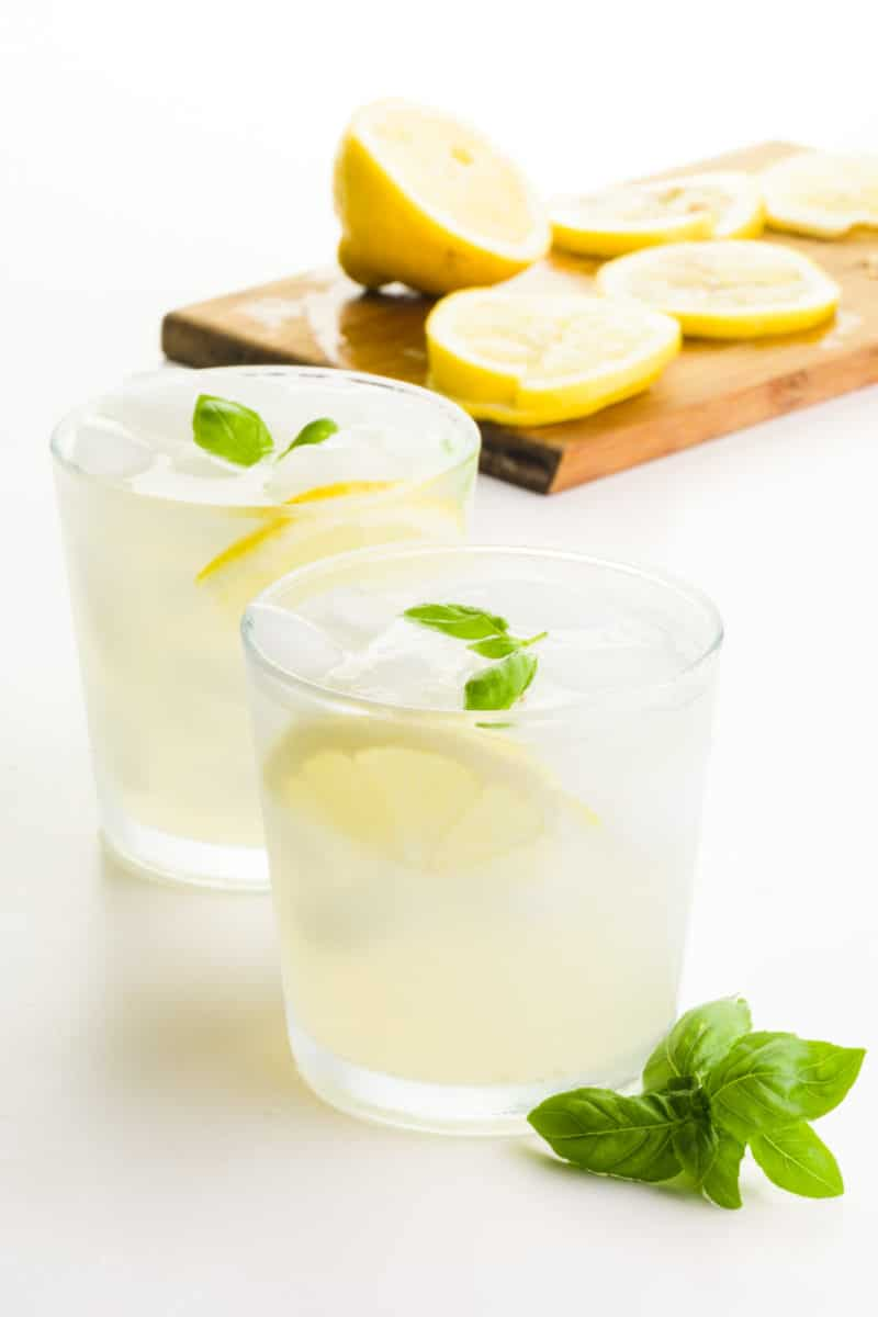 Two glasses hold lemonade. There's sprigs of basil in front of the glass and a cutting board with freshly cut lemons behind it.