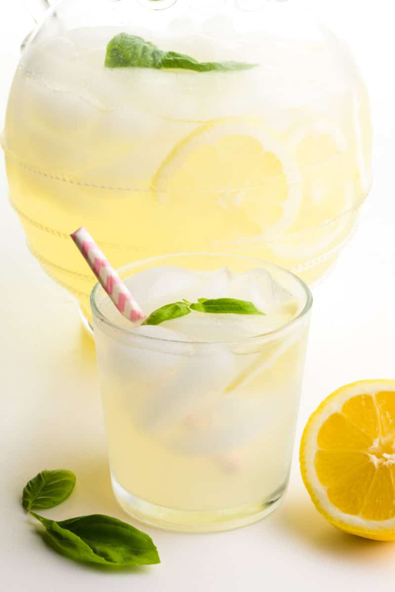A glass sits in front of a pitcher. Both hold lemonade with fresh lemons and basil leaves.