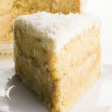A slice of vegan coconut cake on a plate with the rest of the cake behind it.