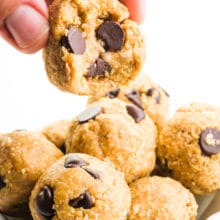 A hand holds a cookie dough ball over a bowl of more of the treats.