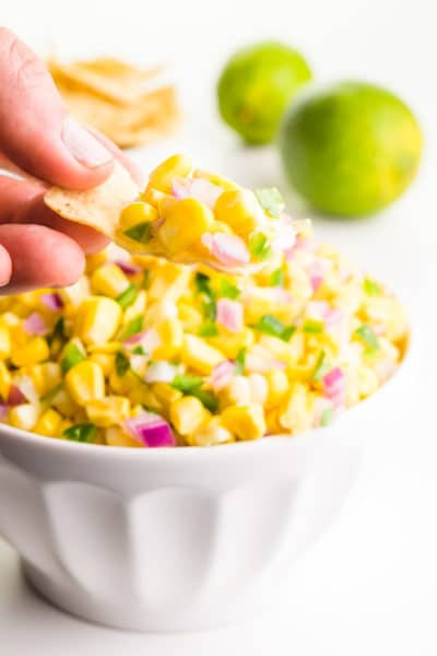 A hand holds a tortilla chip with corn salsa on it. It's sitting above a bowl full of the salsa. There are limes behind it.