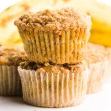 Two muffins are stacked on top of each other with more muffins and bananas behind them.