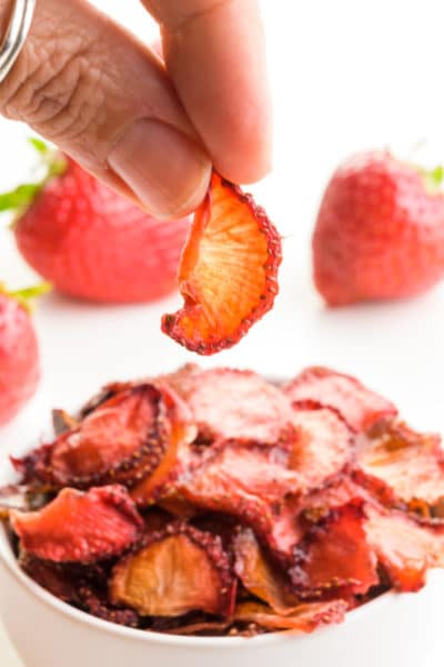 A hand holds a dried strawberry over a bowl of dried strawberry slices. There are fresh strawberries behind the bowl.