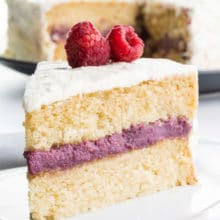 A slice of raspberry coconut cake on a plate sits in front of the rest of the cake.