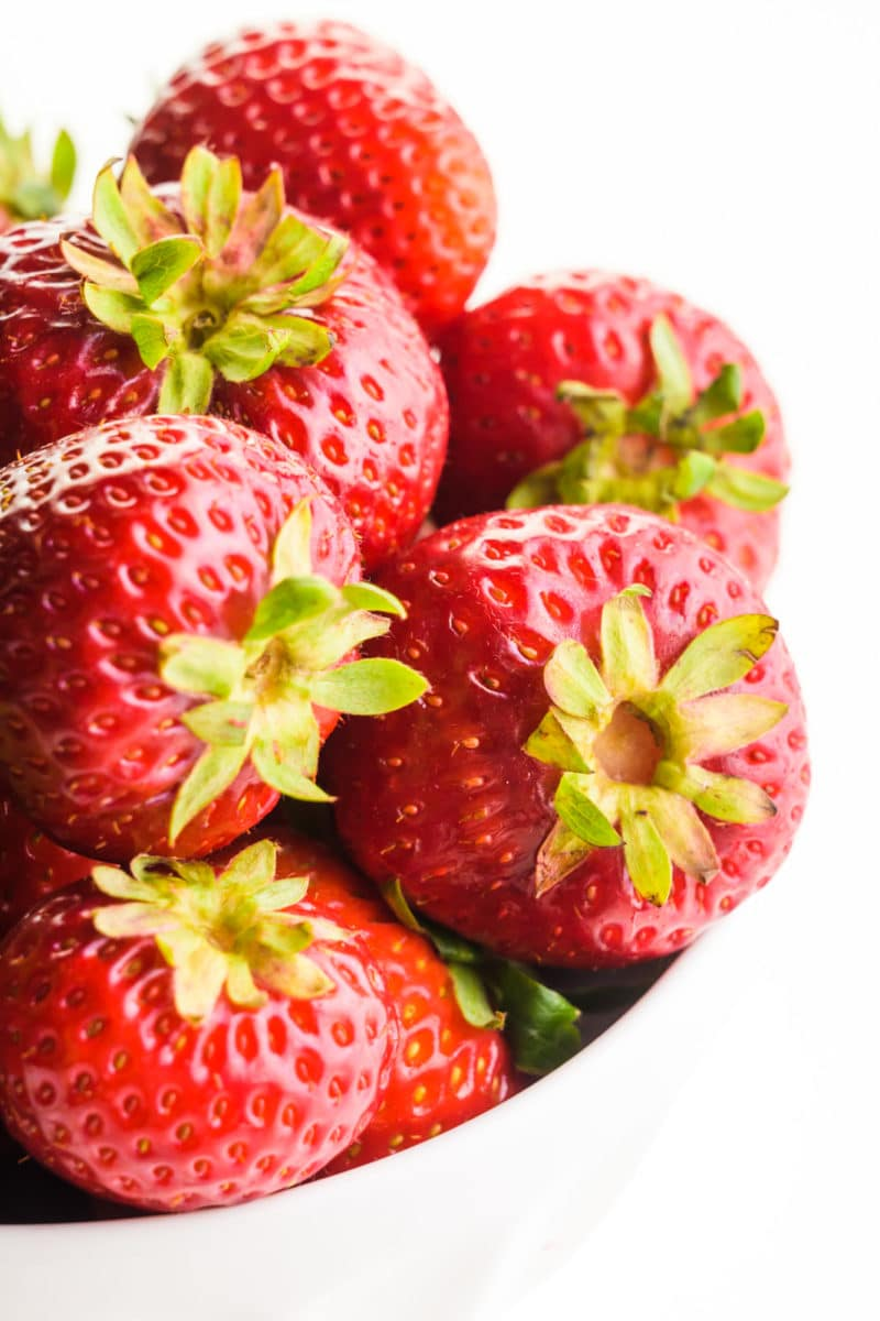 A bowl holds several fresh strawberries.