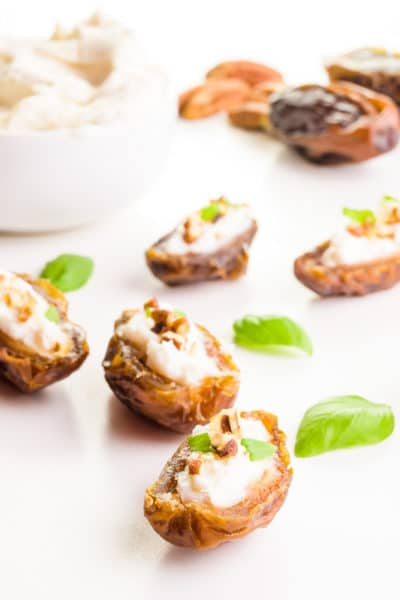 Several stuffed dates with basil leaves between them and cream cheese in a bowl behind it.