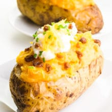 Two vegan twice baked potatoes sit on plates, with vegan bacon, sour cream, and cheese on top.