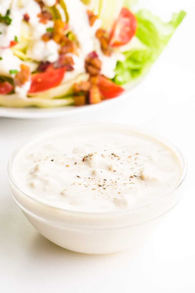 A bowl of vegan blue cheese dressing sits in front of a salad with dressing and toppings.