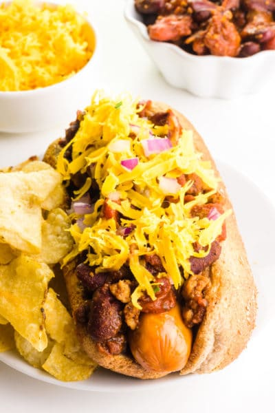 A vegan chili dog has a bowl of cheese and a bowl of chili behind it.