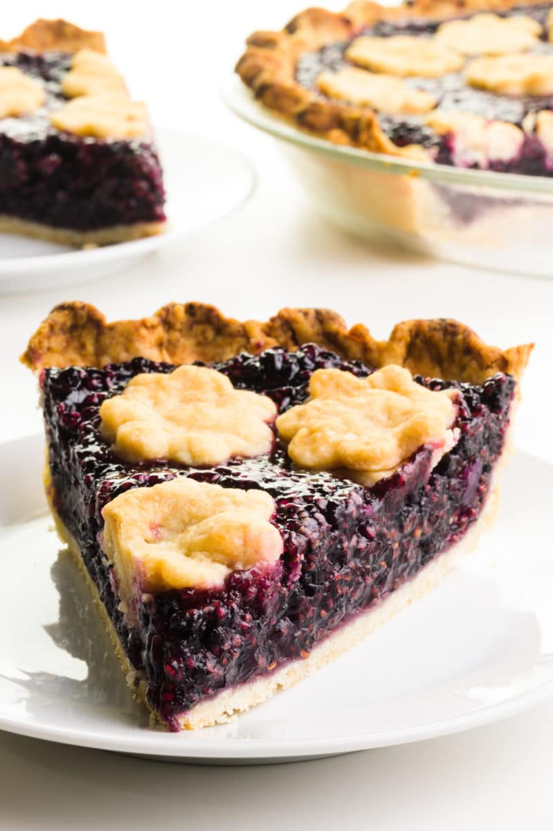 A slice of elderberry pie sits on a plate. There's another slice behind it and the rest of the pie too.