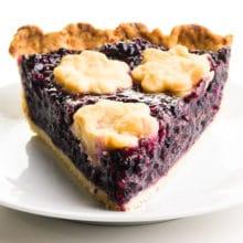 A slice of elderberry pie on a plate.