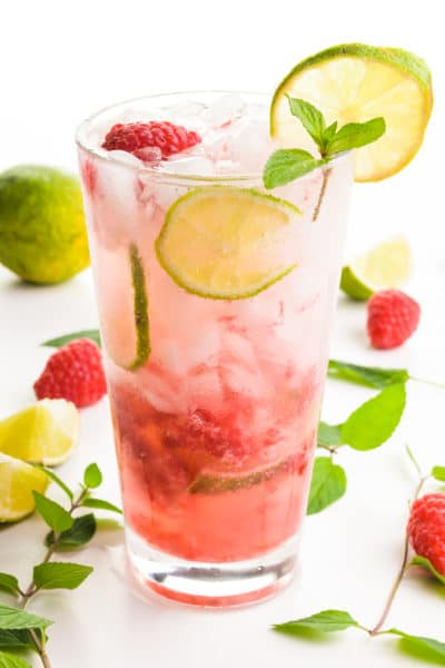 A glass holds a red beverage with slices of lime, mint, and raspberries both in the glass and around the glass too.