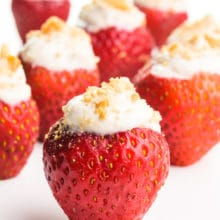 Vegan stuffed strawberries sit on a white counter. Each of them has graham cracker crumbs on top.
