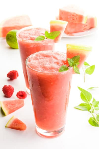 Two glasses full of watermelon slushies have raspberries and mint leaves around them. There are watermelon wedges as garnishes in the drink and also sitting behind the drinks too.