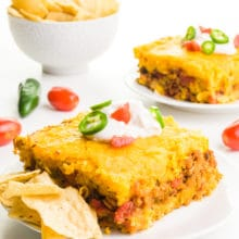 Two plates hold slices of taco cornbread casserole. There's a bowl of tortilla chips behind it.