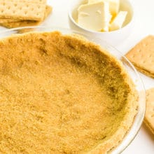 A graham cracker crust is in a glass pie pan. There are graham crackers and vegan butter around it.
