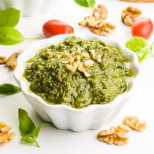 A bowl of walnut pesto has chopped walnuts on top. It's surrounded by walnuts, fresh basil leaves, and cherry tomatoes.