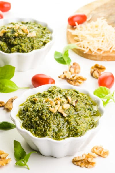 Two bowls hold walnut pesto, topped with chopped walnuts. Around the bowls are cherry tomatoes, basil leaves, and vegan parmesan cheese.