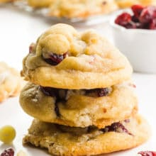 A stack of white chocolate cranberry cookies sits in front of more cookies. There are dried cranberries and white chocoalte chips around them as well.