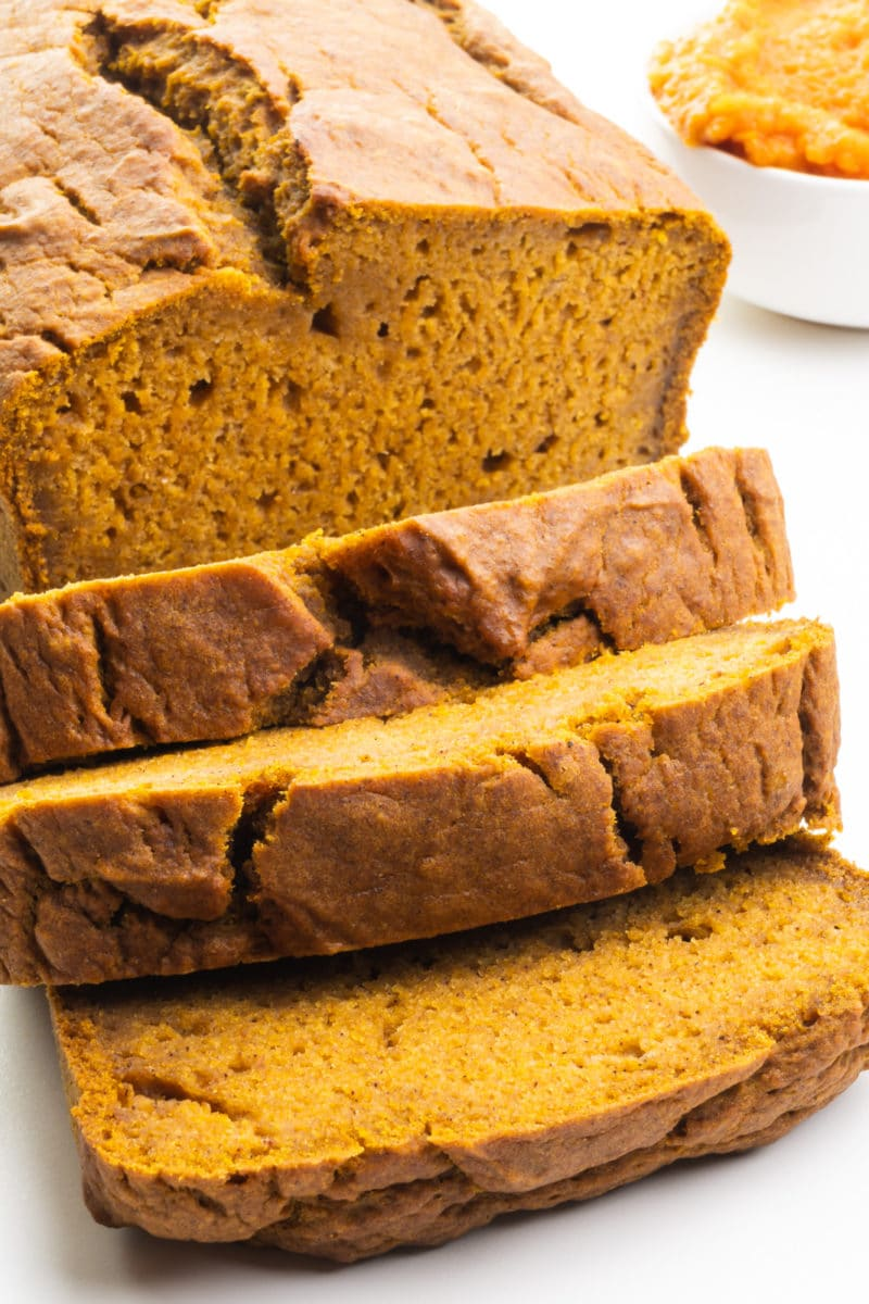 A loaf of vegan pumpkin bread has several slices cut. There's a bowl of Pumpkin Puree next to the loaf.